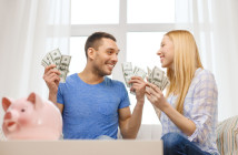 love, family, finance, money and happiness concpet - smiling couple with money and piggybank ot tabl