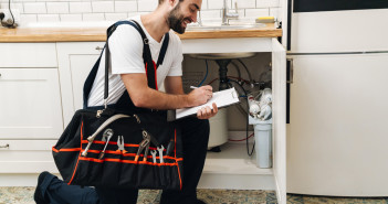 Image of plumber man with equipment and clipboard working in apartment